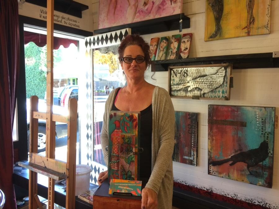 Traci+Owens+holding+a+replica+of+the+utility+box+she+painted.